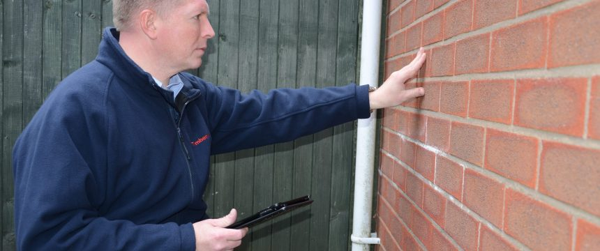 Man inspecting a wall for dampness