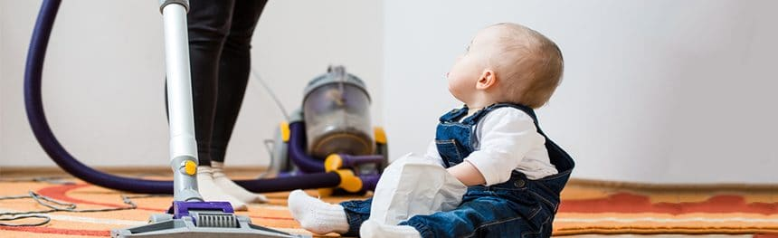 Child on floor with a vacuum cleaner