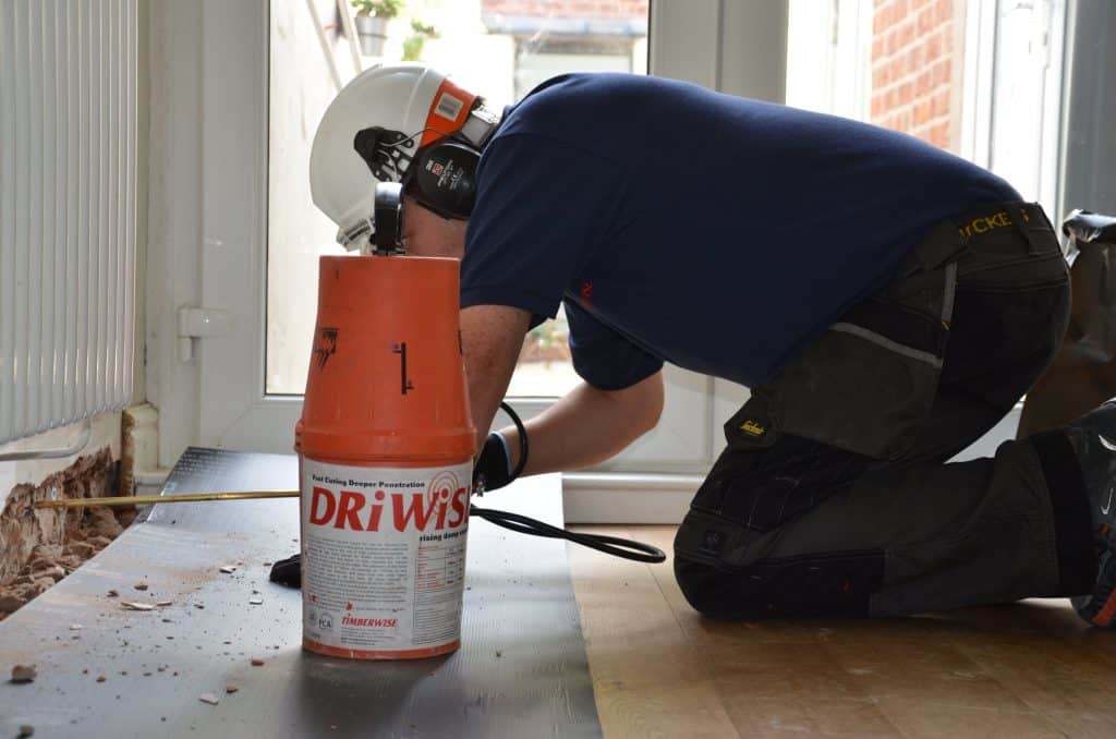 Technician applying a damp proof course