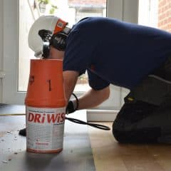 Technician on his knees applying a damp proof course