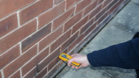 Man testing for dampness in a wall
