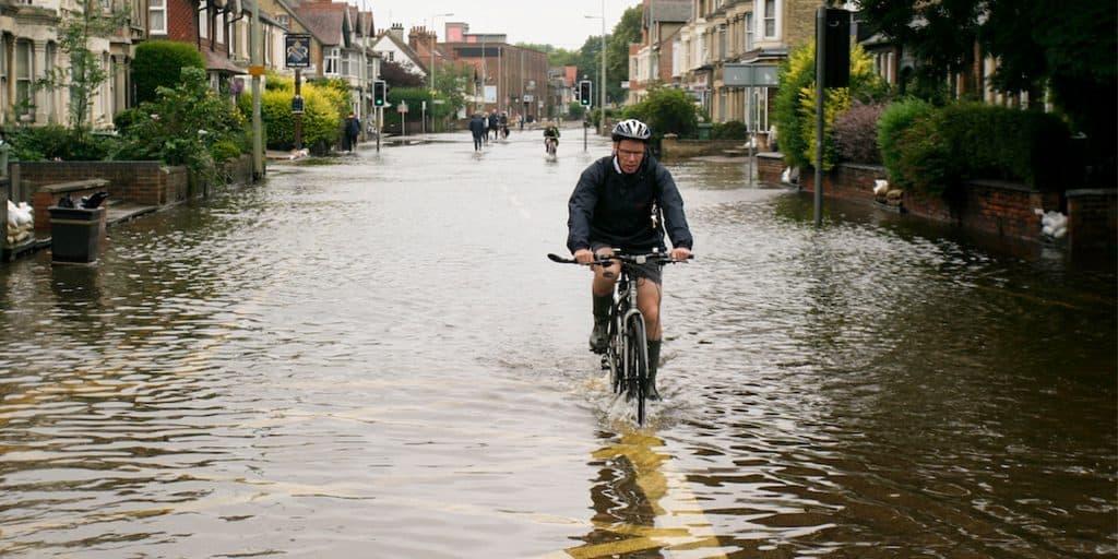 Cyclist cycling through flood water