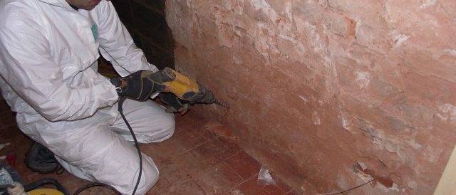 Technician carrying out damp proofing treatment