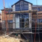 A new build property with scaffolding on the outside and a basement room