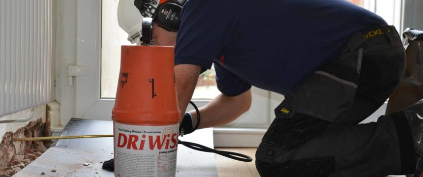 Technician applying damp proof injection cream