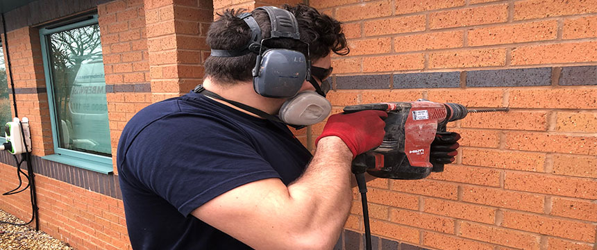 Technician carrying out cavity wall tie replacement