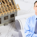 Man with plans and a half build house behind him