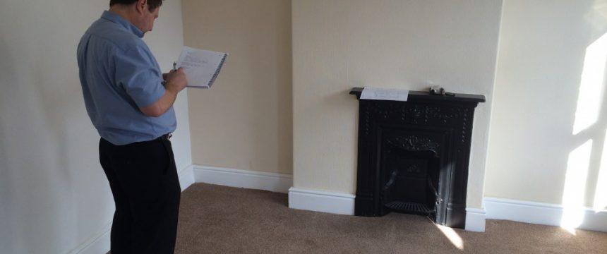 Male surveyor inspecting an empty lounge